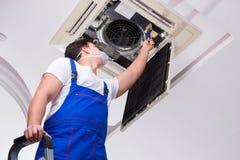 Ο εργαζόμενος που επισκευάζει τη μονάδα ανώτατου κλιματισμού Στοκ Φωτογραφία