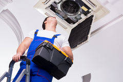 Ο εργαζόμενος που επισκευάζει τη μονάδα ανώτατου κλιματισμού Στοκ φωτογραφία με δικαίωμα ελεύθερης χρήσης