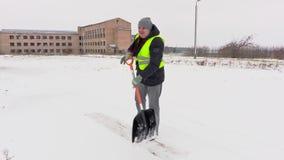 Ο εργαζόμενος που χρησιμοποιεί το φτυάρι χιονιού και παίρνει το σπάσιμο φιλμ μικρού μήκους
