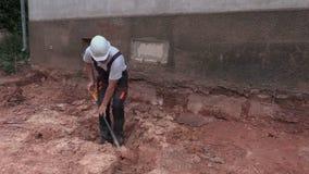 Ο εργαζόμενος σκάβει έξω αλεμένος στην τάφρο απόθεμα βίντεο
