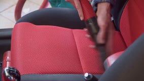 Ο εργαζόμενος σκουπίζει το εσωτερικό αυτοκινήτων με τη μαύρη και κόκκινη κινηματογράφηση σε πρώτο πλάνο καθισμάτων με ηλεκτρική σ