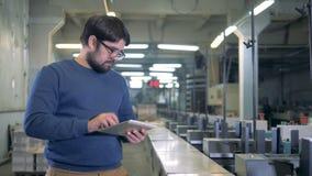 Ο εργαζόμενος σπιτιών εκτύπωσης στέκεται δίπλα στις βιομηχανικές μηχανές φιλμ μικρού μήκους