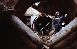 Ο εργαζόμενος στέκεται κοντά στη σωλήνωση κάτω από την κατασκευή στοκ εικόνες