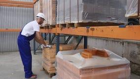 Ο εργαζόμενος στα κόκκινα τούβλα ελέγχου αποθηκών εμπορευμάτων συσσώρευσε στους κύβους κόκκινοι φραγμοί των τούβλων στο απόθεμα Τ φιλμ μικρού μήκους