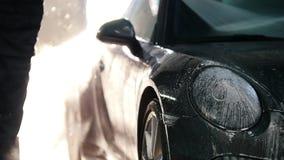 Ο εργαζόμενος στην αυτόματη υπηρεσία πλένει ένα αυτοκίνητο πολυτέλειας από τις μάνικες νερού, backlight