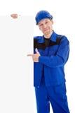 Ο εργαζόμενος στην μπλε ομοιόμορφη υπόδειξη στον κενό πίνακα διαφημίσεων σημαδιών Στοκ φωτογραφία με δικαίωμα ελεύθερης χρήσης
