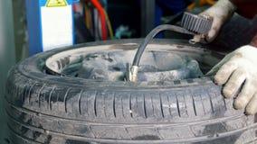 Ο εργαζόμενος στην υπηρεσία αυτοκινήτων διογκώνει τα ελαστικά αυτοκινήτου με τον αέρα - μηχανικό εργαστήριο απόθεμα βίντεο