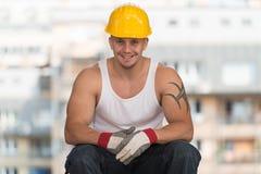 Ο εργαζόμενος στηρίζεται τη συνεδρίαση στο τούβλο Στοκ εικόνες με δικαίωμα ελεύθερης χρήσης