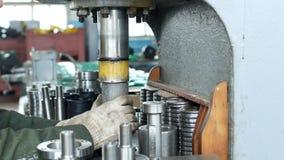 Ο εργαζόμενος στις εγκαταστάσεις πιέζει το ρουλεμάν στην πλήμνη χρησιμοποιώντας μια μηχανή Τύπου, συγκεντρώνοντας την πλήμνη, συγ απόθεμα βίντεο