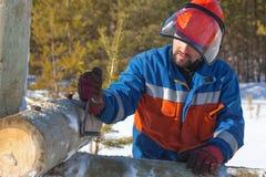 Ο εργαζόμενος στις μπλε φόρμες τοποθετεί τα ηλεκτροφόρα καλώδια υποστήριξης Στοκ Εικόνες