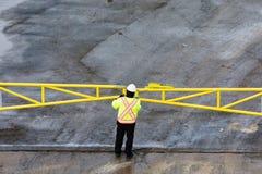 Ο εργαζόμενος στον ιματισμό ασφάλειας κλειδώνει την κίτρινη πύλη μετάλλων στοκ εικόνα με δικαίωμα ελεύθερης χρήσης