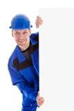 Ο εργαζόμενος στον μπλε ομοιόμορφο πίνακα διαφημίσεων σημαδιών εκμετάλλευσης κενό Στοκ εικόνα με δικαίωμα ελεύθερης χρήσης
