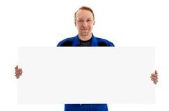 Ο εργαζόμενος στον μπλε ομοιόμορφο πίνακα διαφημίσεων σημαδιών εκμετάλλευσης κενό Στοκ Φωτογραφίες