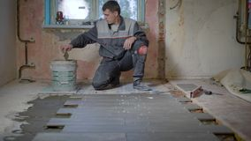 Ο εργαζόμενος στους ελέγχους μορφής οικοδόμησης το επίπεδο της επιφάνειας στο κεραμικό κεραμίδι, βάζει έπειτα το τσιμέντο στο πάτ φιλμ μικρού μήκους