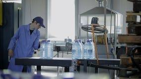 Ο εργαζόμενος στο εργοστάσιο παίρνει τα συσκευασμένα μπουκάλια του νερού από τη ζώνη μεταφορέων απόθεμα βίντεο