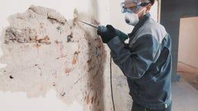 Ο εργαζόμενος στο προστατευτικό κοστούμι κατεδαφίζει τον τοίχο ασβεστοκονιάματος Βρώμικος, σκληρή δουλειά equipment personal prot φιλμ μικρού μήκους
