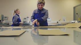 Ο εργαζόμενος στο σακάκι κόβει το έγγραφο στον πίνακα γυαλιού στο εργαστήριο φιλμ μικρού μήκους