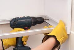 Ο εργαζόμενος συγκεντρώνει τα έπιπλα στην κουζίνα Στοκ φωτογραφία με δικαίωμα ελεύθερης χρήσης