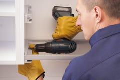 Ο εργαζόμενος συγκεντρώνει τα έπιπλα στην κουζίνα Στοκ Φωτογραφία