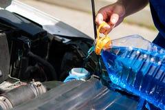Ο εργαζόμενος υπηρεσιών, χύνει στο ρευστό πλυντηρίων δεξαμενών για τα παράθυρα αυτοκινήτων πλύσης στοκ φωτογραφίες