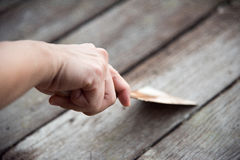 Ο εργαζόμενος χεριών ξύνει την ξύλινη επιφάνεια ομαλή με το trowel Στοκ Φωτογραφίες