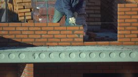 Ο εργαζόμενος χτίζει έναν τοίχο των τούβλων ο οικοδόμος σε ένα κτήριο κάνει την πλινθοδομή ο οικοδόμος στο εργοτάξιο οικοδομής κά απόθεμα βίντεο