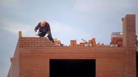 Ο εργαζόμενος χτίζει τον τοίχο των τούβλων οικοδόμος στην οικοδόμηση της κάνοντας πλινθοδομής ο οικοδόμος στο εργοτάξιο οικοδομής απόθεμα βίντεο