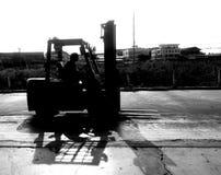 Ο εργαζόμενος forklift περιμένει σηκώνει το φορτίο χτυπημένος από τη γραπτή φωτογραφία στοκ φωτογραφία