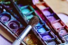Ο εργασιακός χώρος της βούρτσας χρωμάτων καλλιτεχνών και των ρόδινων γαρίφαλων Στοκ φωτογραφία με δικαίωμα ελεύθερης χρήσης