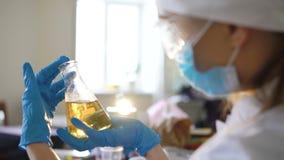 Ο εργαστηριακός βοηθός εξετάζει την καφετιά ουσία απόθεμα βίντεο