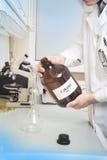 Ο εργαστηριακός βοηθός χύνει από ένα μπουκάλι με το γραπτό τύπο του οινοπνεύματος στοκ φωτογραφίες με δικαίωμα ελεύθερης χρήσης