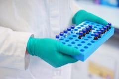 Ο εργαστηριακός επιστήμονας κρατά ένα πλαστικό κιβώτιο με τα δείγματα του διαφανούς υγρού στα φιαλίδια στοκ φωτογραφία