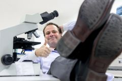 Ο ερευνητής χαλαρώνει με τους αντίχειρες χειρονομίας επάνω Στοκ Φωτογραφίες