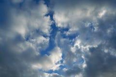 Ο ερπυσμός σύννεφων βροχής και στις δύο πλευρές και καλύπτει το σαφή μπλε ουρανό στοκ εικόνα