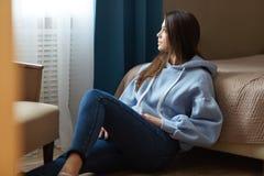 dbe97ea79c0 Ο εσωτερικός πυροβολισμός της στοχαστικής μελαχροινής μαλλιαρής γυναίκας  που ντύνεται στην μπλε μπλούζα, τζιν,