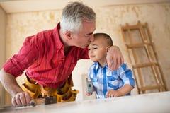 Ο ευγενής παππούς αγκαλιάζει και φιλά το βοηθό εγγονών του Στοκ Εικόνες