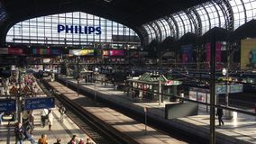 Ο ευρύς πυροβολισμός του κεντρικού σταθμού του Αμβούργο με τους ταξιδιώτες waitung για το τραίνο τους στον ήλιο λάμπει/καθιερώνον απόθεμα βίντεο