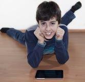 Ο ευτυχής έφηβος κοιτάζει στο ψηφιακό σημειωματάριο Στοκ φωτογραφία με δικαίωμα ελεύθερης χρήσης