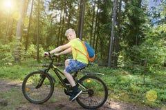 Ο ευτυχής έφηβος οδηγά ένα ποδήλατο στο ξύλο πεύκων, στην ηλιόλουστη ημέρα Στοκ Φωτογραφία