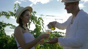 Ο ευτυχής αγρότης θεραπεύει το αγροτικό κορίτσι με το κρασί της συγκομιδής φθινοπώρου και φλερτάρει στη φυτεία αμπελώνων στο φωτε απόθεμα βίντεο