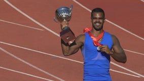 Ο ευτυχής αθλητής που δαγκώνει το μετάλλιό του που παρουσιάζει αυτό είναι χρυσός, θρίαμβος εορτασμού νικητών απόθεμα βίντεο
