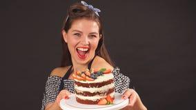 Ο ευτυχής αρχιμάγειρας ζύμης κοριτσιών κρατά έναν δίσκο με το κέικ φιλμ μικρού μήκους