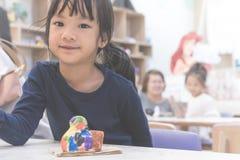 Ο ευτυχής ασιατικός σπουδαστής χρωματίζει το αντικείμενο στην τάξη τέχνης Στοκ εικόνα με δικαίωμα ελεύθερης χρήσης