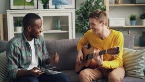 Ο ευτυχής αφροαμερικάνος τύπων και καυκάσιος μαθαίνει να παίζει την κιθάρα χρησιμοποιώντας την ταμπλέτα που γελά και που κάνει έπ φιλμ μικρού μήκους