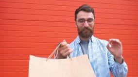 Ο ευτυχής γενειοφόρος τύπος πορτρέτου με τα γυαλιά παίρνει τις τσάντες στα χέρια του αγορές στο κατάστημα φιλμ μικρού μήκους