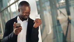 Ο ευτυχής ενθαρρυντικός εορτασμός επιχειρηματιών αφροαμερικάνων εξετάζοντας το κύτταρο τηλεφωνά και κρατώντας ένα μεγάλο χρηματικ απόθεμα βίντεο