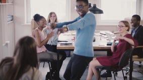 Ο ευτυχής επιχειρηματίας αφροαμερικάνων μπαίνει στο γραφείο, γιορτάζει τη νίκη με τον τρελλό χορό, υψηλός-fives-μέγιστοι συνάδελφ απόθεμα βίντεο