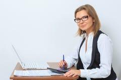 Ο ευτυχής εργαζόμενος γραφείων θηλυκών κάθεται στο γραφείο της και Στοκ φωτογραφία με δικαίωμα ελεύθερης χρήσης