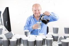 Ο ευτυχής εργαζόμενος γραφείων πίνει πάρα πολύ καφέ Στοκ εικόνες με δικαίωμα ελεύθερης χρήσης