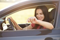 Ο ευτυχής θηλυκός οδηγός κρατά τα κλειδιά από το αυτοκίνητο, που πηγαίνει να το πωλήσει, διαφημίζει το αυτοκίνητο υψηλής ταχύτητα στοκ φωτογραφία με δικαίωμα ελεύθερης χρήσης